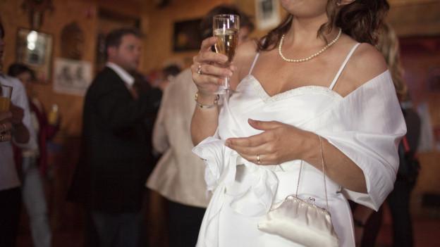 Braut in weissem Kleid hält ein Glas in der Hand.
