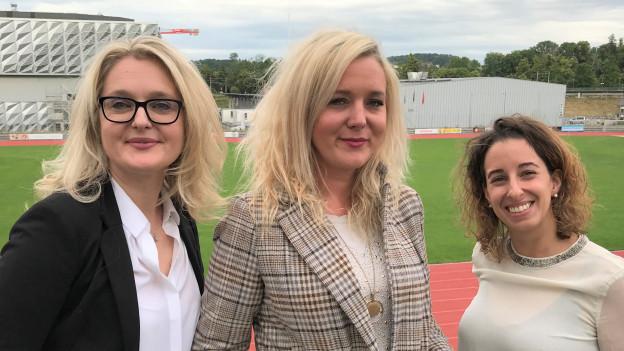 Drei Frauen stehen in einem Stadion