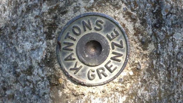 Aufschrift auf Boden: «Kantonsgrenze»