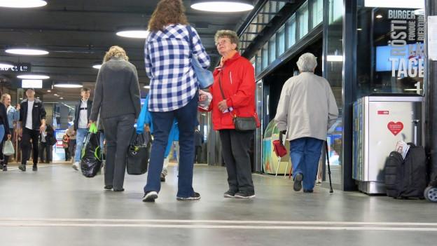 Frau, die im Bahnhof Hefte verkauft, andere Passanten