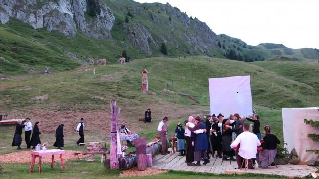 Szene aus Frelichtspiel: Schauspieler auf grüner Wiese, Bergkulisse