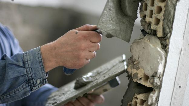 Ein Handwerker verputzt eine Wand. Deutsche Handwerker kommen weniger in die Schweiz.
