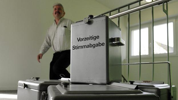 Volle Wahlurnen warten unter Bewachung darauf, geleert zu werden.