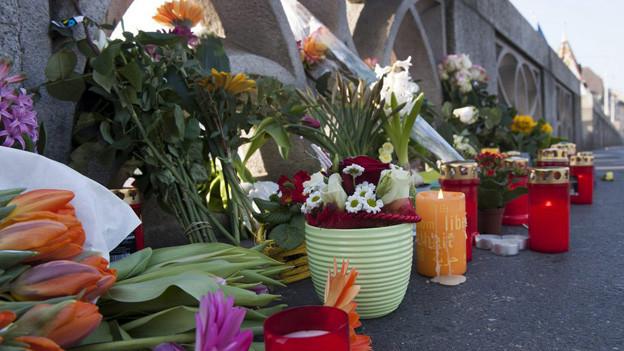 Blumen und Kerzen am Geländer Mittleren Rheinbrücke am 15.3.2012.