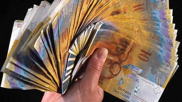 Eine Hand hält viele 10-Franken-Geldscheine