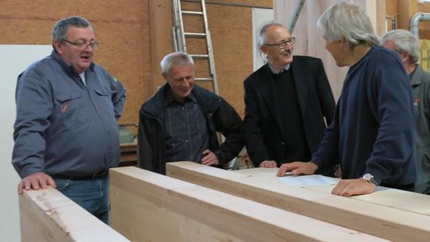 Männer stehen um verarbeitetes Holz