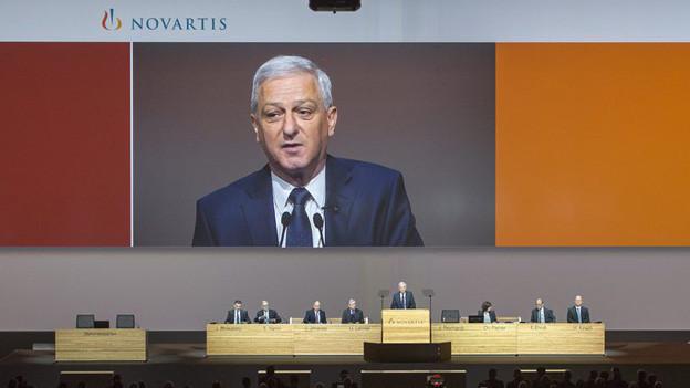 VR-Präsident Jörg Reinhardt am Rednerpult vor Sreen mit Reinhardt.