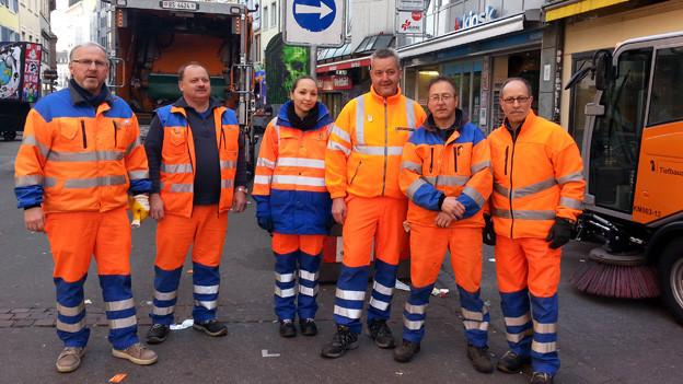 Sechs Stadtreiniger in orangen Overalls
