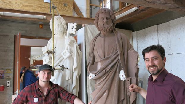 Petrus-Statue zwischen Steinmetz J. Gysin und Hüttenmeister R. Keller.