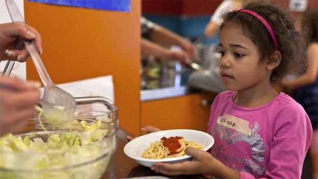 Ein Kind bekommt einen Teller Spaghetti serviert