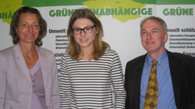 Kandidaten der Grünen-Unabhängigen posieren vor einem Plakat