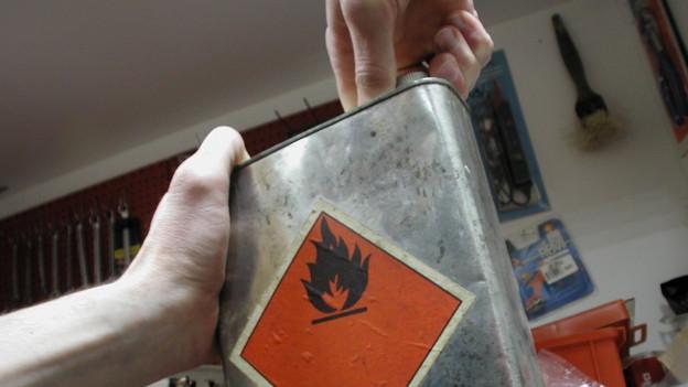 Jemand hält einen Kanister mit einem brennbaren Stoff