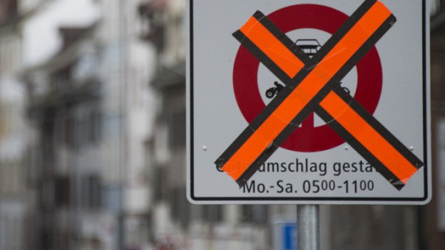 Vor der Rheingasse steht ein Strassenschild, das teilweise mit Klebband verdeckt ist.