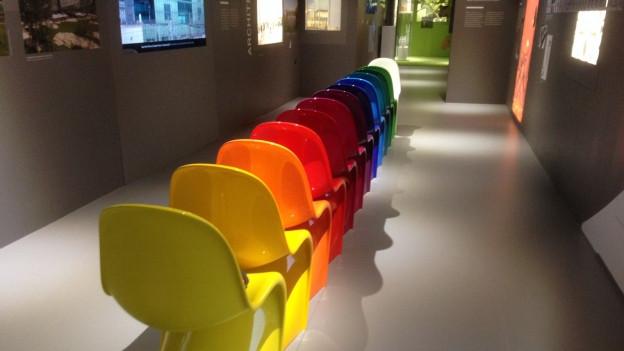 Eine Reihe bunter Plastikstühle in der Schweizer Ausstellung in Milano
