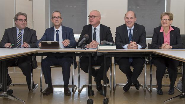 Die fünf Regierungsmitglieder am Tisch vor den Medien