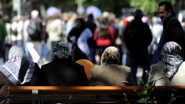Vier Frauen mit Kopftuch auf Parkbank