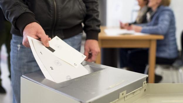 Jemand wirft seine Abstimmungsunterlagen ein