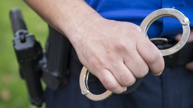 Ein Polizist hält eine Handschelle