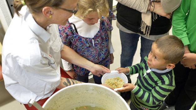 Flüchtlingskind bekommt einen Teller Essen