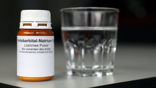 Wasserglas und Medikamentenfläschchen