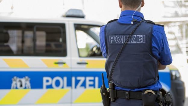 Ein Polizist steht vor einem Polizeiauto