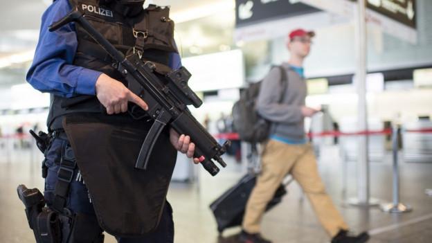 Polizist mit Maschinenpistole und kugelsicherer Weste