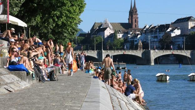 Leute beim Sonnenbaden am Kleinbasler Rheinufer