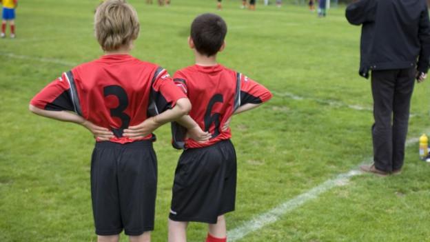 Zwei Jungen im Fussballdress am Spielfeldrand