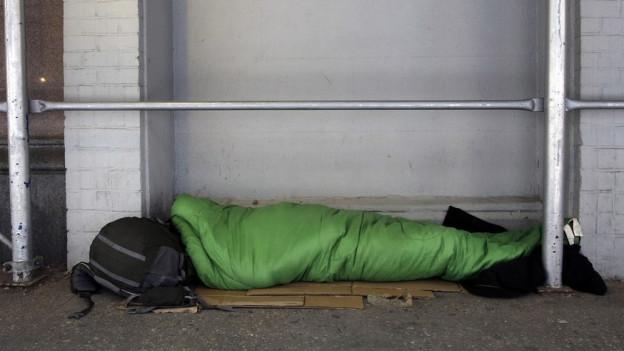 Obdachloser in Schlafsack auf Strasse