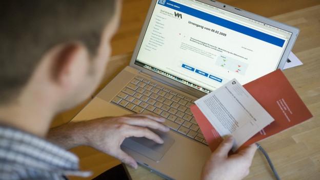 Mann vor Computer mit Abstimmungsunterlagen