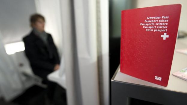 Ein Schweizer Pass im Vordergrund, eine Person in der Unschärfe im Hintergrund.