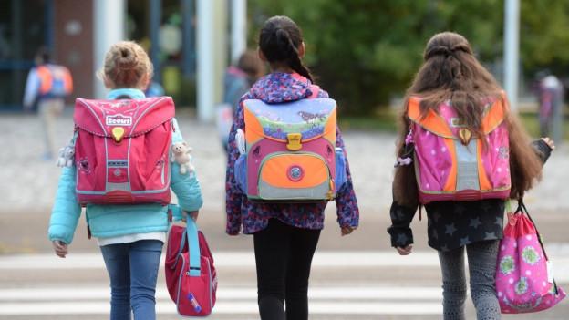 Drei Schülerinnen mit Schulsack