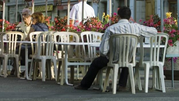 Strassencafé mit Plastikstühlen