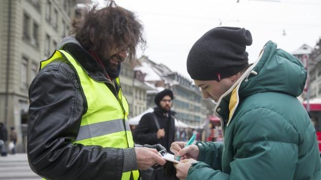 Mann in grüner Veste lässt Passanten unterzeichnen