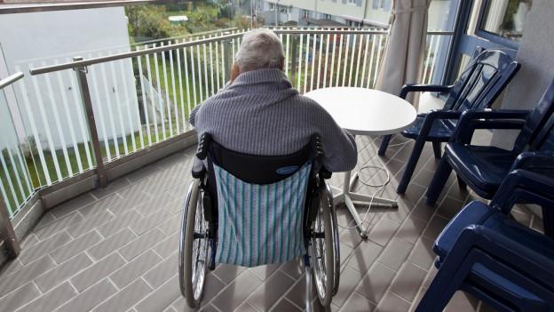 Alte Frau auf Balkon des Pflegheims