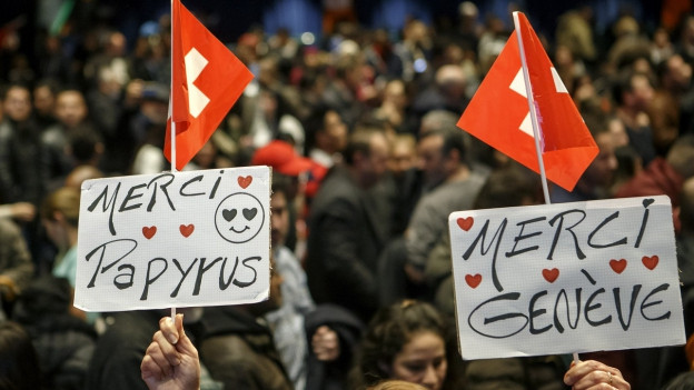 "Kundgebung mit Plakat ""Merci Papyrus"""