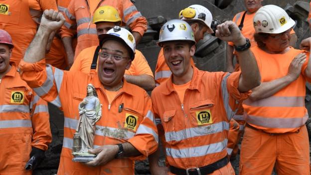 Bauarbeiter feiern den Durchstich.