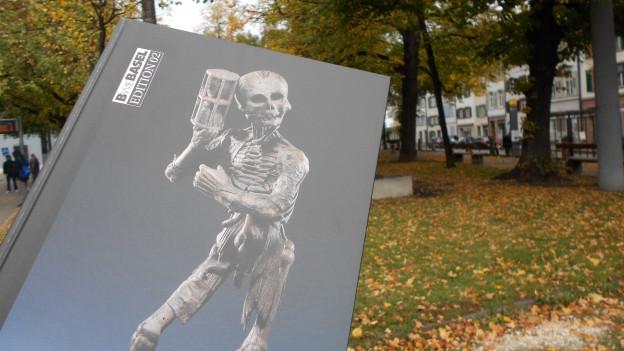 Ein Buch mit einem Skelett in einem Park.