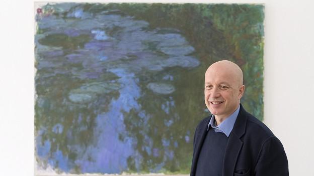 Sam Keller, Direktor der Fondation Beyeler, lächelt vor dem Kunstwerk «Seerosen»