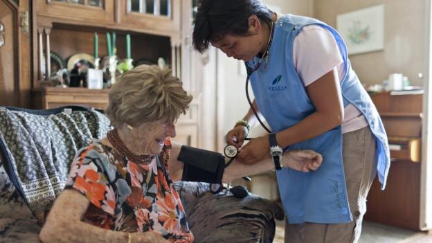 Pflegerin misst den Blutdruck einer älteren Patientin