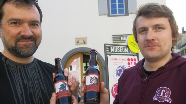 Marc Limat und Niklaus Niederhauser mit einer Flasche Bier