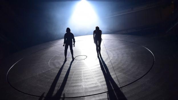 Zwei Menschen stehen auf einer grossen Metallscheibe.
