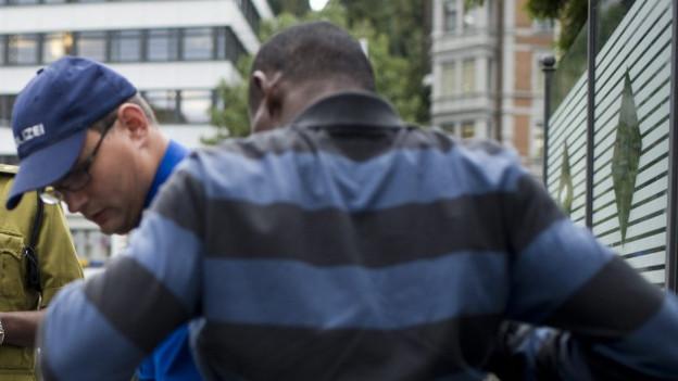 Polizist kontrolliert dunkelhäutigen Mann