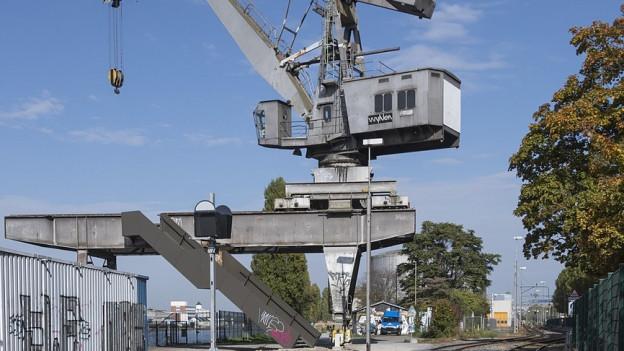 Ein grosser Hafenkran steht am Rheinufer, im Vordergrund sind Bahngeleise zu sehen