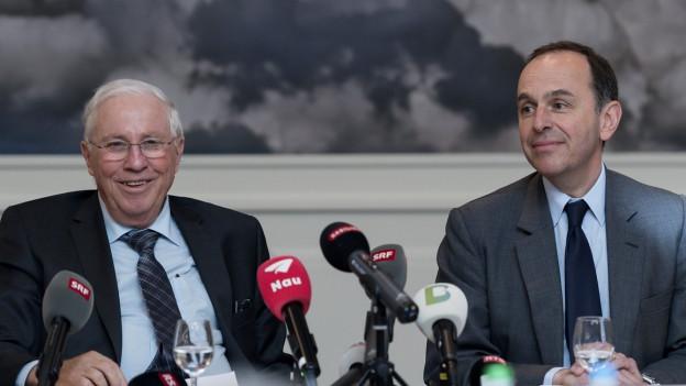 Christoph Blocher und Pietro Supino sitzen an einem Tisch mit Mikrofonen im Vordergrund