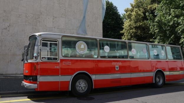 Ein Roter Bus steht vor der Universität am Petersplatz