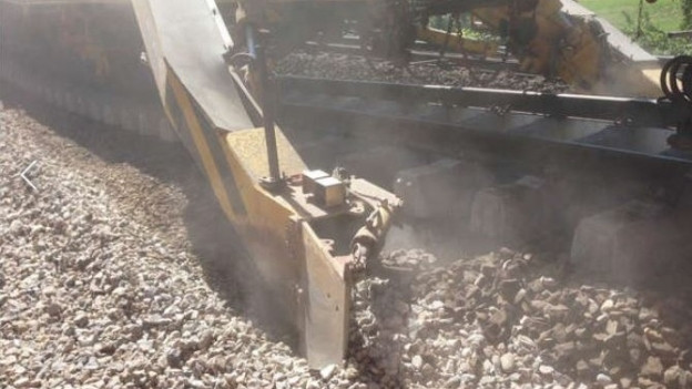 Eine riesige Maschine sorgt dafür, dass die Gleise von Schotter befreit werden.