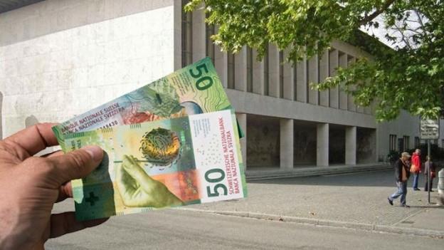 Hand mit Geldnoten vor Unigebäude