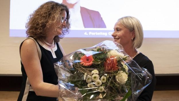 Eine Frau überreicht einer zweiten Frau Blumen