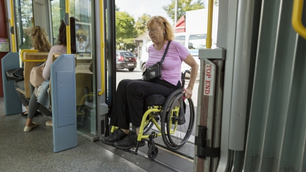 Eine Frau in einem Rollstuhl steigt in ein Tram